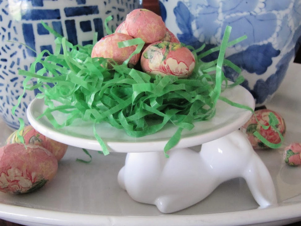 white cake plate with a rabbit holding grass and colorful easter eggs