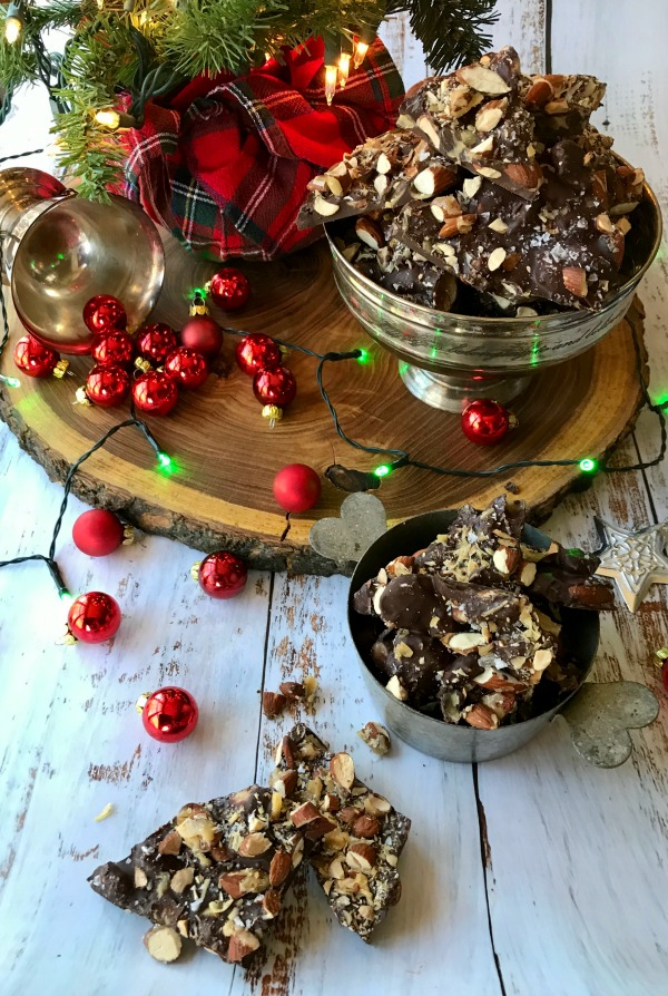 Chocolate almond bark in silver dish with christmas tree and lights