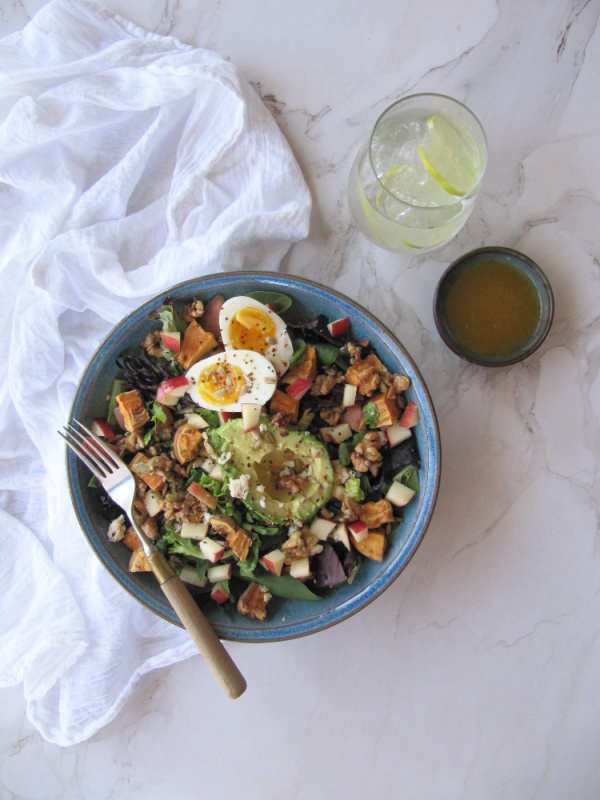 Roasted Sweet potato spinach salad with eggs, avocado and nuts.