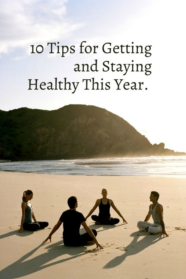 people on beach practicing yoga with text 10 tips for getting and staying healthy this year
