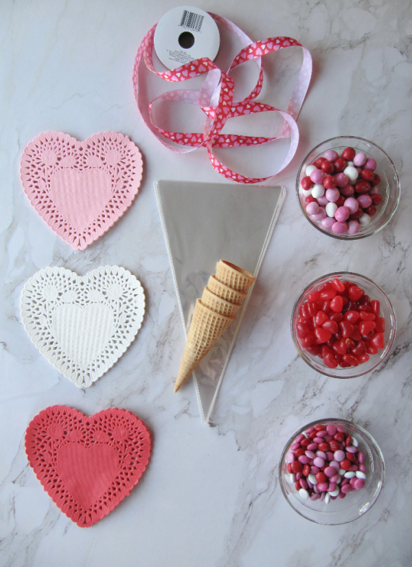 Red, white, pink heart doilies and three bowls of valentines day candy