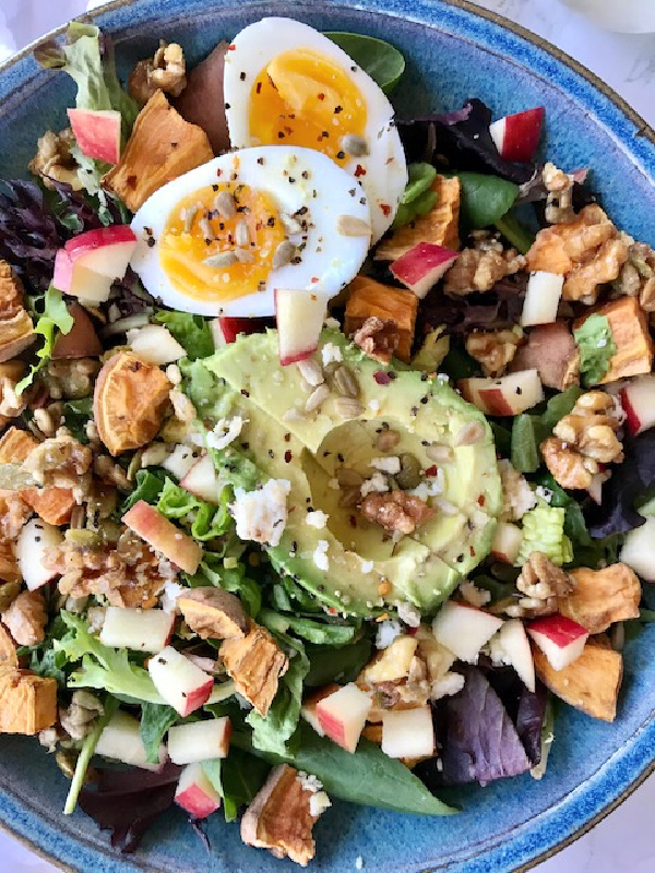 Blue Bowl with spinach egg avocado apple and nut salad