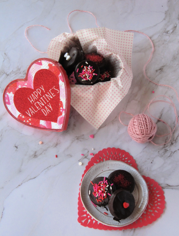 Heart shaped bow filled with chocolate covered Oreo cookies decorated with sprinkles