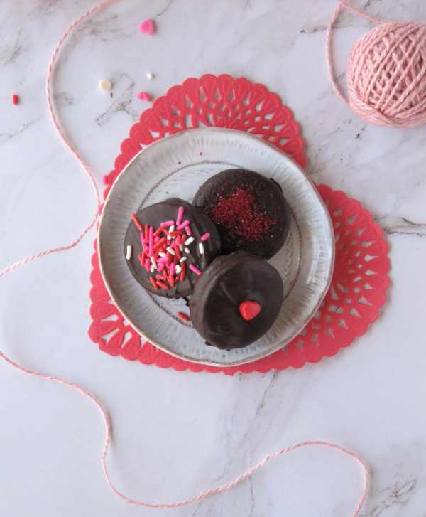 Chocolate covered Oreo cookies on a heart shaped plate sitting on a red doily