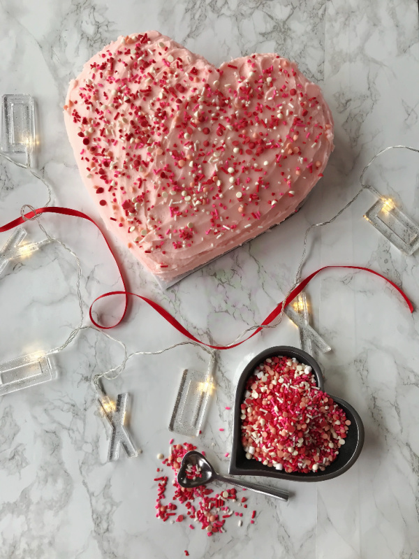 Heart shaped cake with sprinkles and an extra heart shaped bowl of colorful sprinkles