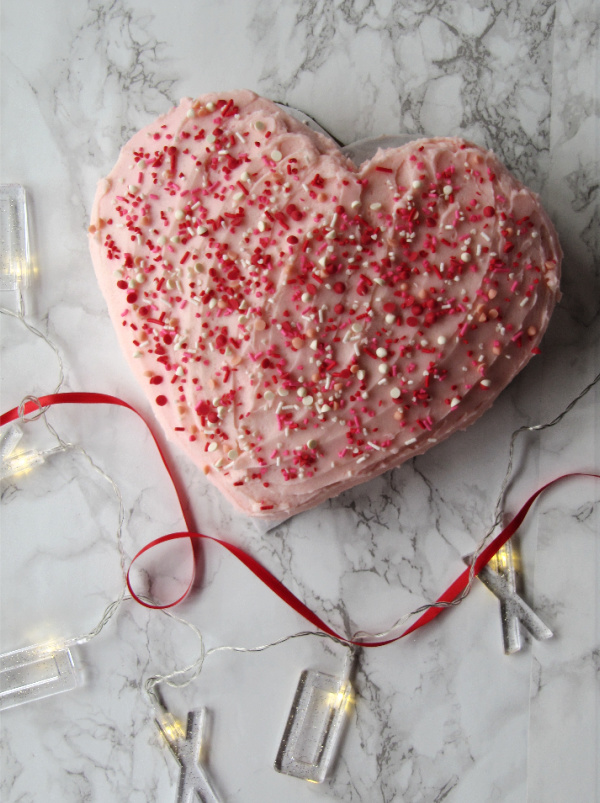 Heart shaped cake with pink frosting and colorful sprinkles