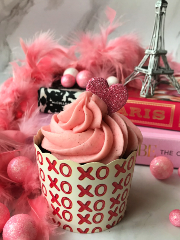 Valentines cupcake with pink frosting in front of pink books with an Eiffel Tower on top
