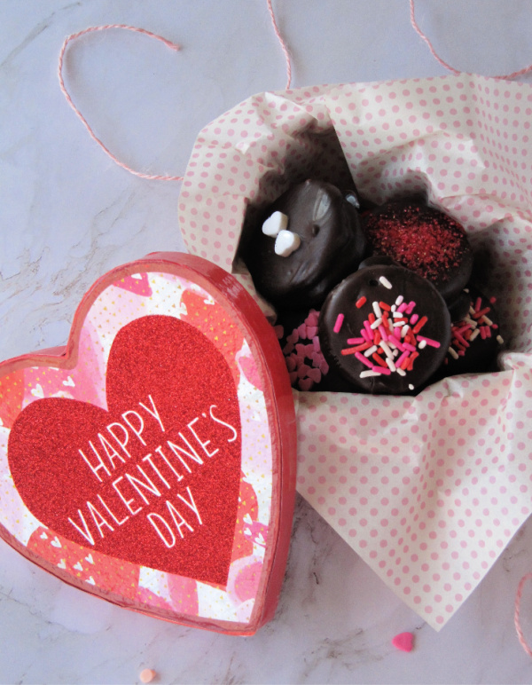 Heart shaped box with the words Happy Valentines day filled with chocolate covered Oreos decorated with colorful sprinkles