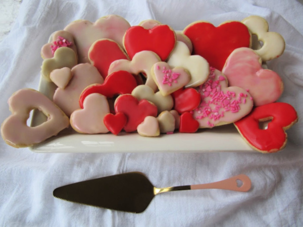 White plate piled high with pink, red and white heart shaped sugar cookies