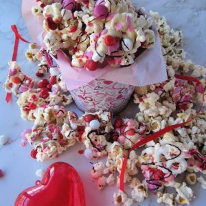 Bucket of chocolate covered popcorn with colored candy and sprinkles and a red plastic heart sitting next to it.