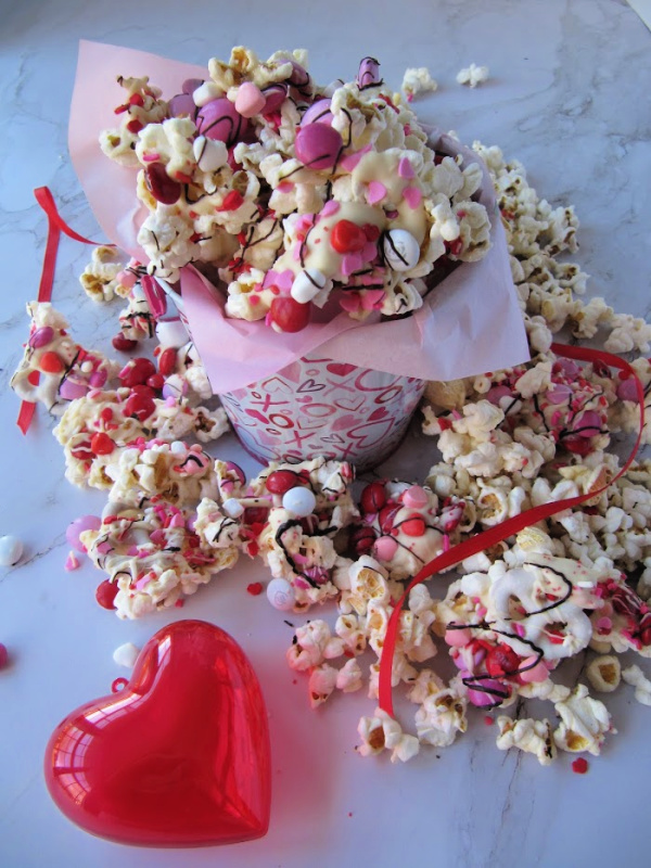 Valentine Popcovered covered in chocolate and candy in a tin bucket surrounded by popcorn and a red plastic heart