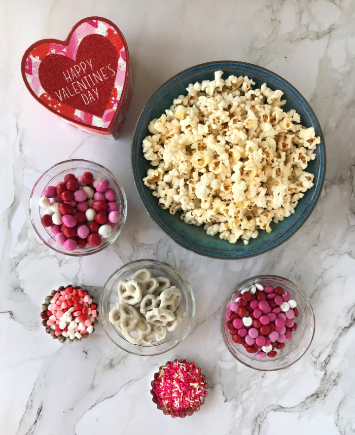 Blue Bowl of Popcorn surrounded by small bowls of colored candy, sprinkles, jimmies and pretzels