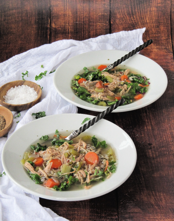 Chicken wild rice soup with kale in white bowls on a wood background