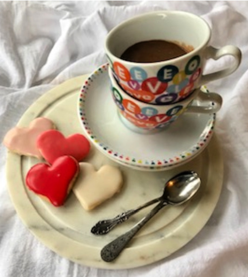 Two cups with hearts sitting on saucers and a marble circle with heart shaped sugar cookies.