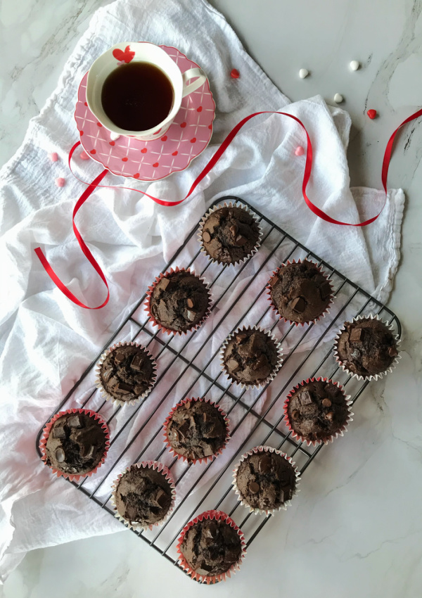 double chocolate muffins on cooling rack with cup of hot chocolate