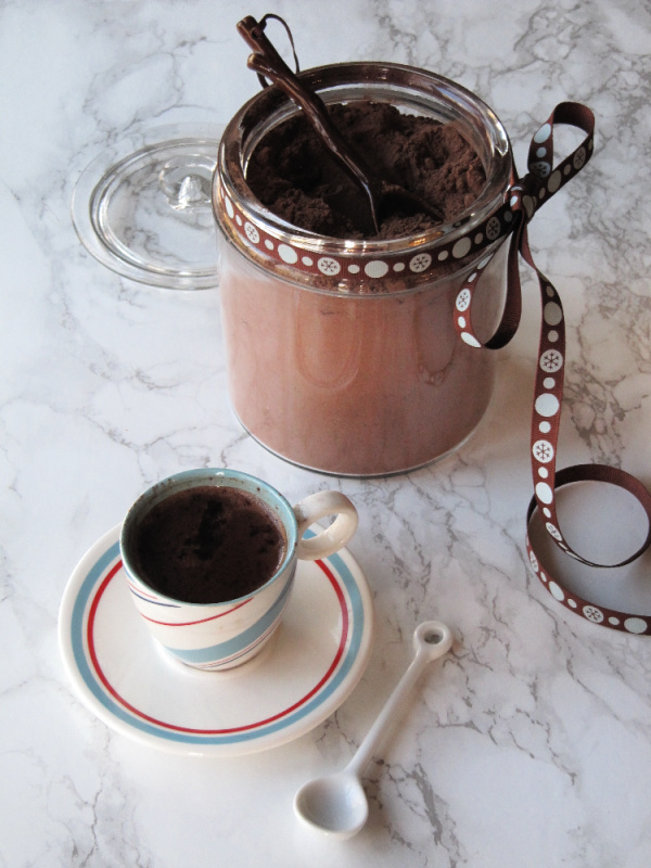 Homemade hot cocoa mix in a glass container with a cup beside it