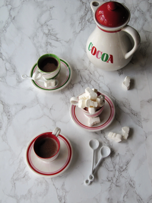 hot cocoa pot and three cups of cocoa with marshmallows