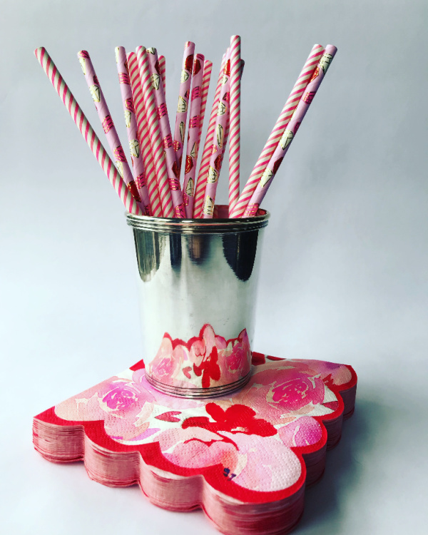 Silver cup with pink straws on a flowered napkin