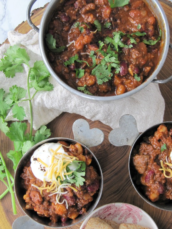 tex-mex-chili in 2 bowls and a pot with cheese and cilantro