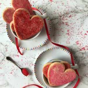 two cups on saucers filled with heart shaped cookies