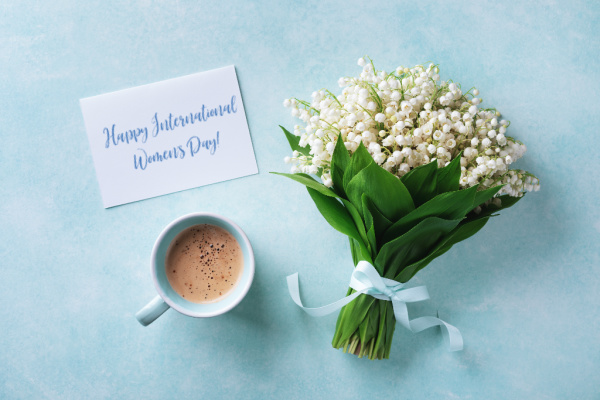 Lily of the valley with a cup of coffee and a sign on blue background