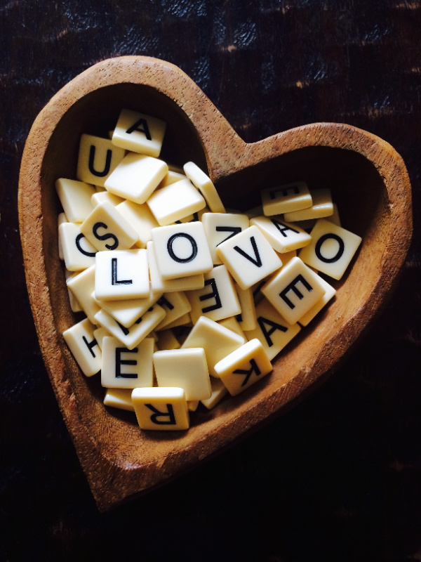 scrabble times in a heart shaped bowl spelling LOVE