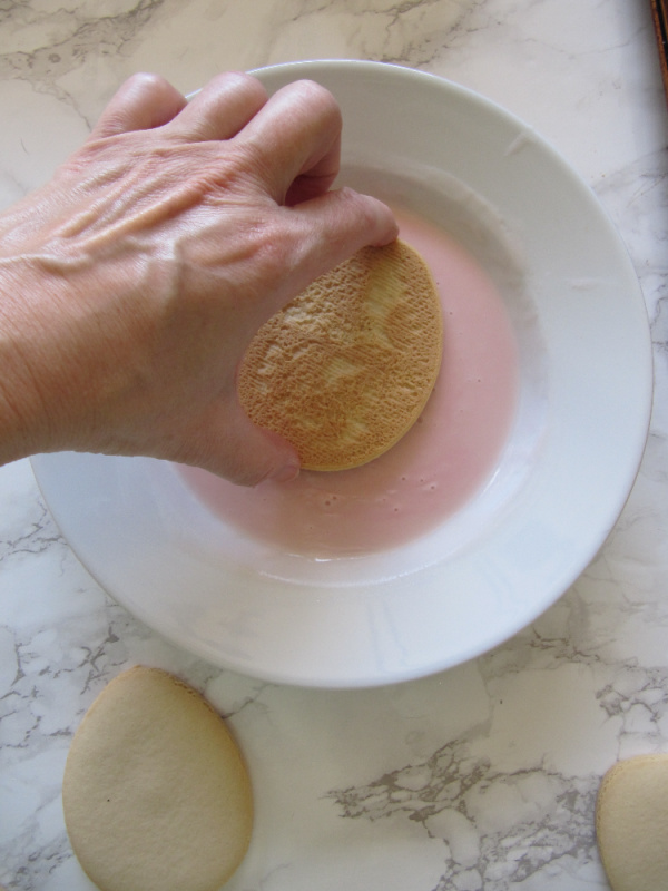 Hand dipping cookie into frosting