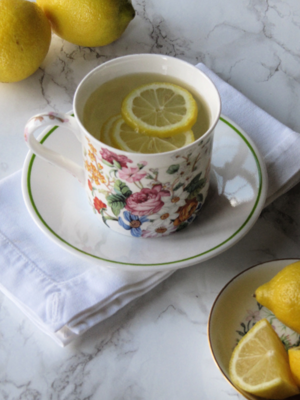lemon water in flowered cup on a saucer with green trim