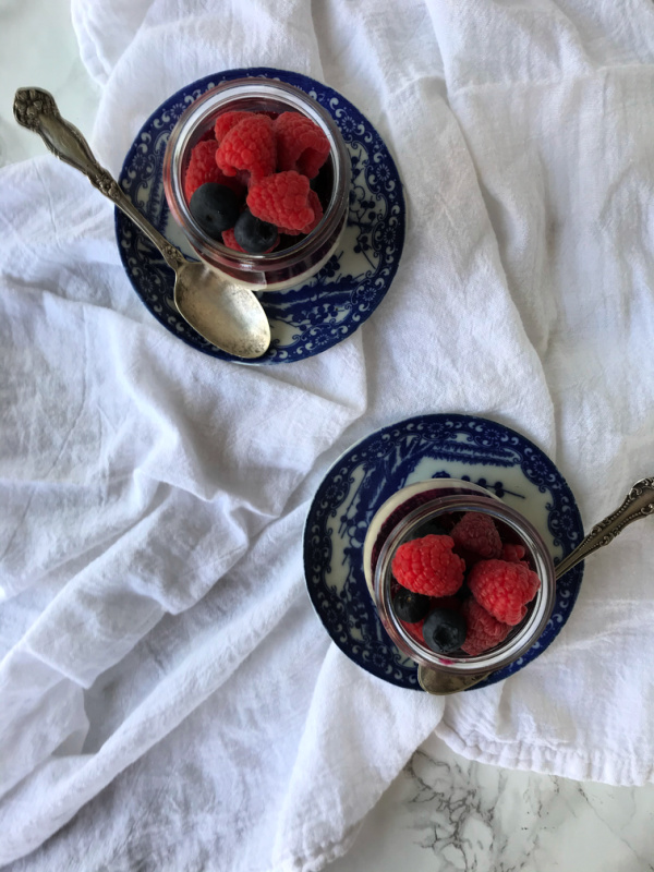 panna cotta in jars with berries on two plates