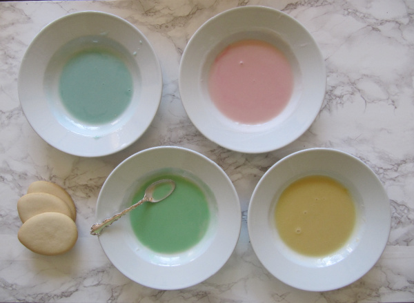 pastel pink green blue and yellow bowls of frosting with egg cookies