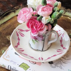 Pink flowers a teacup on a saucer