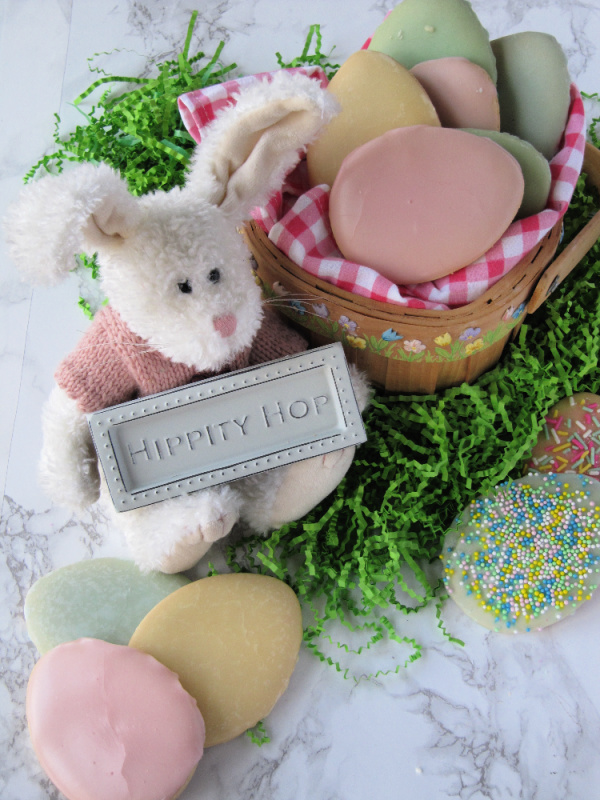 stuffed bunny with a basket of pastel Easter egg cookies
