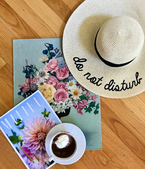 Do not disturb sun hat sitting on top of a flower painting with a milieu magazine and a cup of hot chocolate