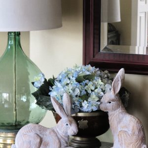two wood easter bunnies a bowl of hydrangeas and a Demi John lamp on a marble table