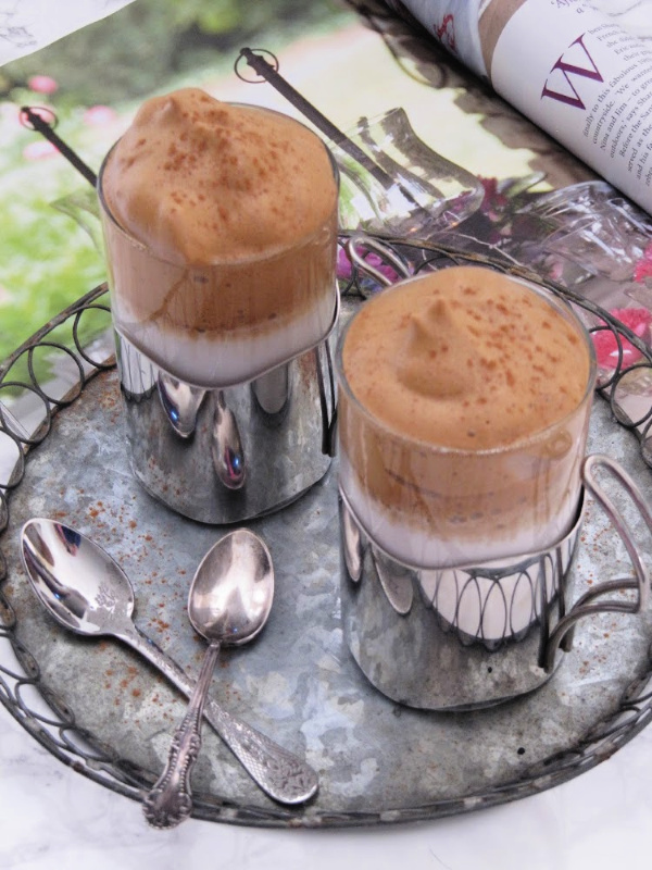 Vanilla Dalgona Whipped Coffee in silver cups on a zinc tray with a magazine