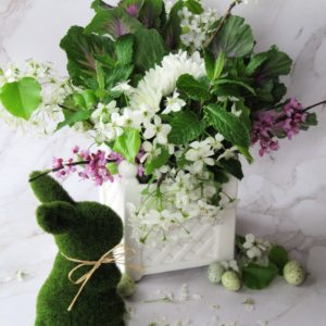 Flower arrangement with cherry blossoms and a moss covered bunny