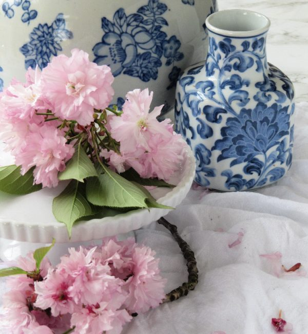pink cherry blossoms on a white cake plate with blue and white chinoiserie vases pinecones and acorns blog