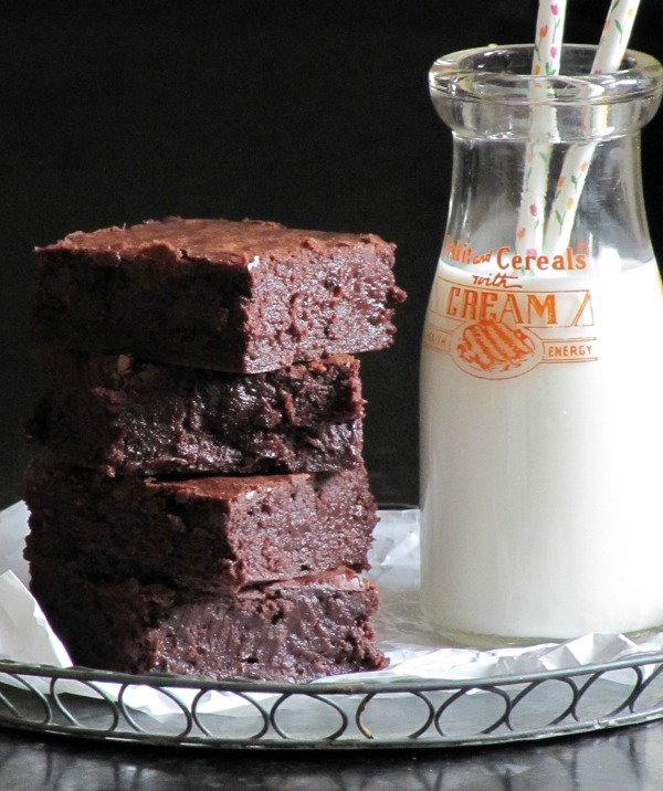 brownies sitting next to a milk bottle with two straws