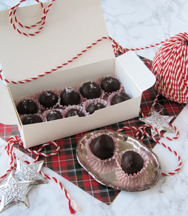 fleur-de-sel-truffles in white box sitting on a plaid square with a ball of twine next to it
