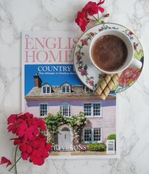 The English Home Magazine with a cup of hot chocolate and a few fuchsia colored geraniums on a white marble background pinecones and acorns blog